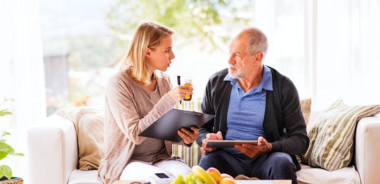 elder man with caregiver with medicine