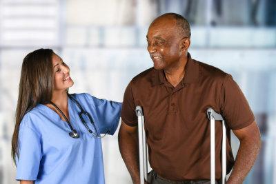 caregiver with elder man smiling